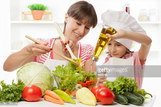 Madre e hija, preparación de fresca ensalada de vegetales
