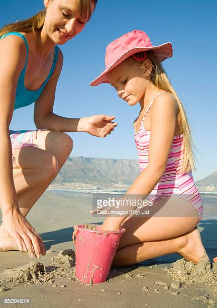Mother and daughter making sand castles on the beach with Table Mountain in the background, Cape Town, Western Cape Province, South Africa
