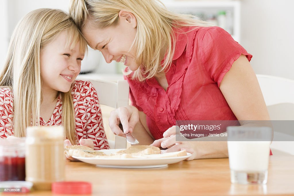 Mother and daughter making sandwich : Stock Photo