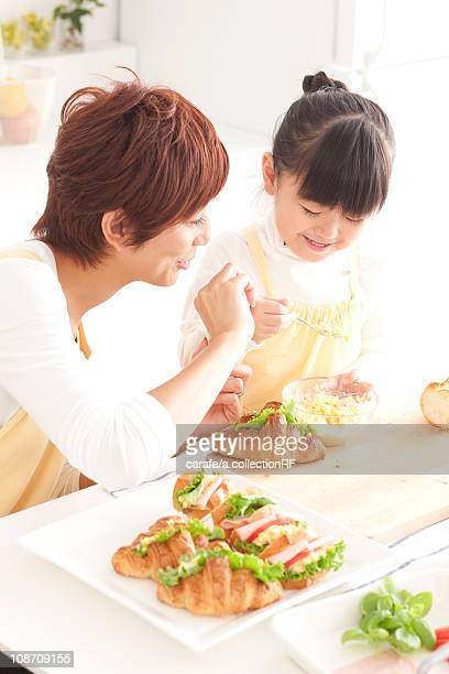 Mother and daughter making sandwiches