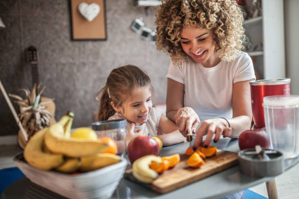 mother and daughter making  smoothie - preparation stock pictures, royalty-free photos & images