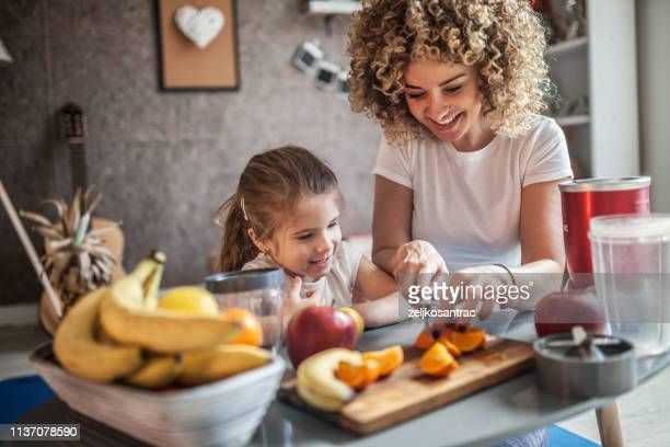 mother and daughter making  smoothie - fruit stock pictures, royalty-free photos & images