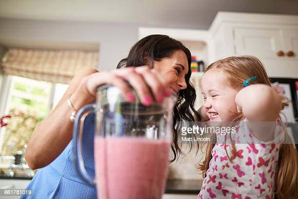 Mother and daughter making smoothies in noisy blender