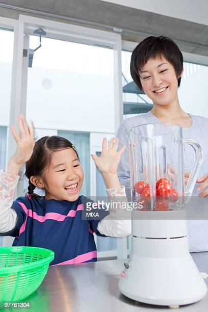 Mother and daughter making tomato juice