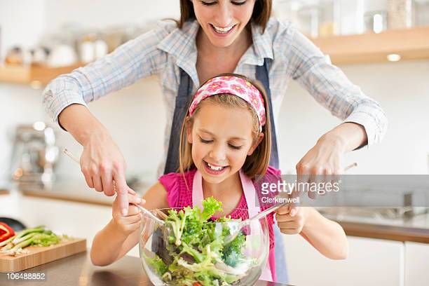 Mother and daughter (8-9) mixing vegetable salad in kitchen