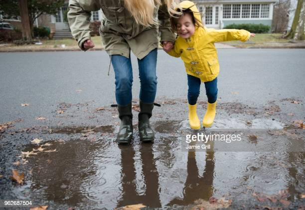 mother and daughter (2-3) near puddle - puddle stock pictures, royalty-free photos & images