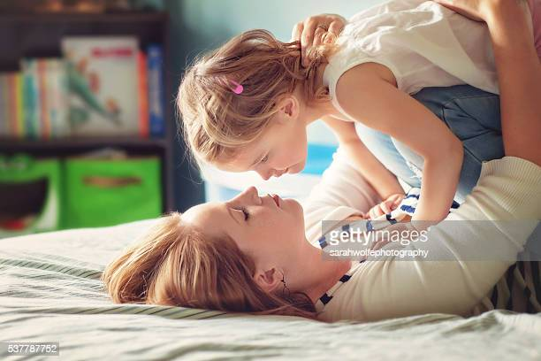 mother and daughter nose to nose while playing on a bed