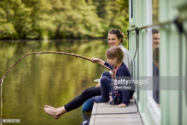 Mother and daughter on a houseboat with girl using stick as fishing rod