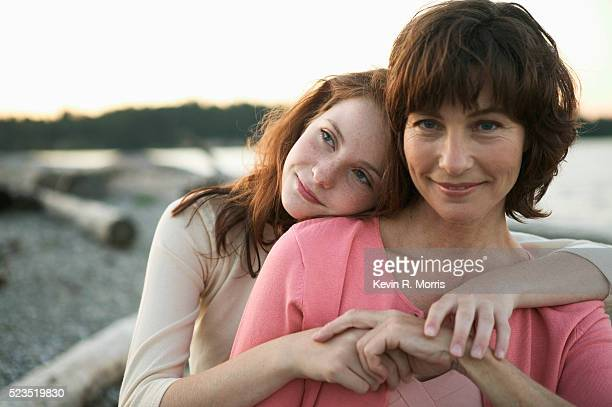 mother and daughter on beach at dusk - tochter stock-fotos und bilder