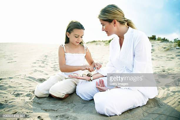 mother and daughter (6-8) on beach, girl lining shells on mother's arm - white pants stock pictures, royalty-free photos & images