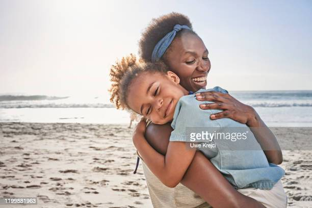 mother and daughter on beach - protection stock pictures, royalty-free photos & images