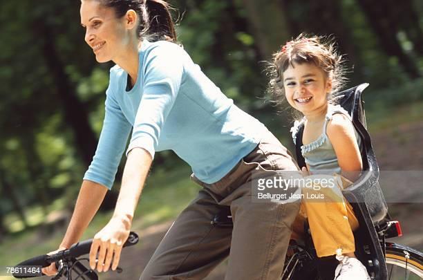 mother and daughter on bike - luggage rack stock photos and pictures