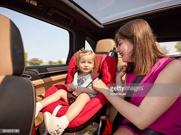 Mother and daughter on car back seat