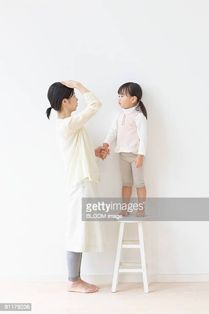Mother and daughter on chair comparing heights