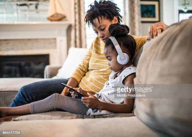 mother and daughter on couch using tablet - electrical equipment stock pictures, royalty-free photos & images