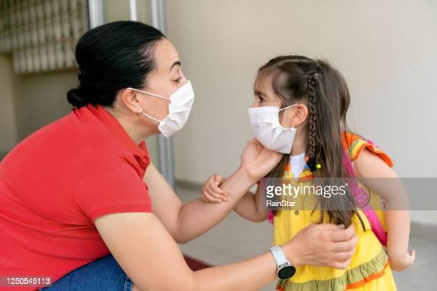 mother and daughter on first school day - servizi per l'infanzia foto e immagini stock