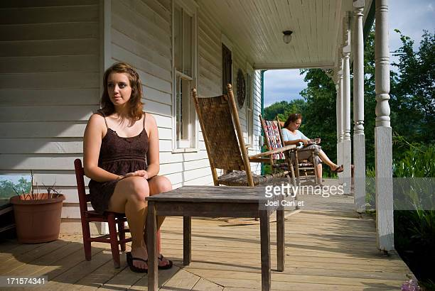 Mother and daughter on front porch of rustic old home