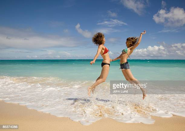 mother and daughter on hawaiian beach - john lund stock pictures, royalty-free photos & images