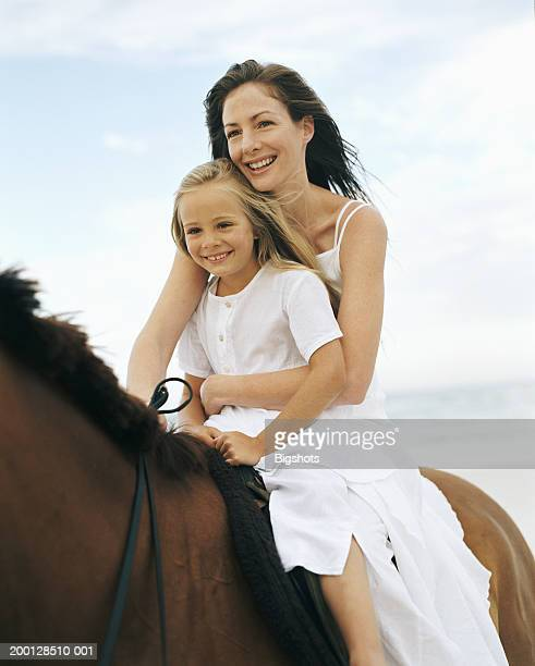 Mother and daughter (5-7) on horseback, smiling
