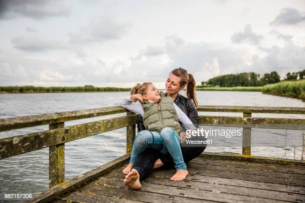 Mother and daughter on jetty at a lake