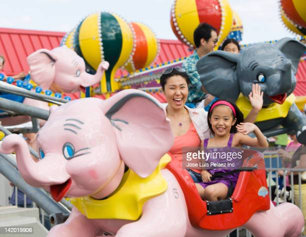 mother and daughter on ride at amusement park - 遊園地の乗り物 ストックフォトと画像