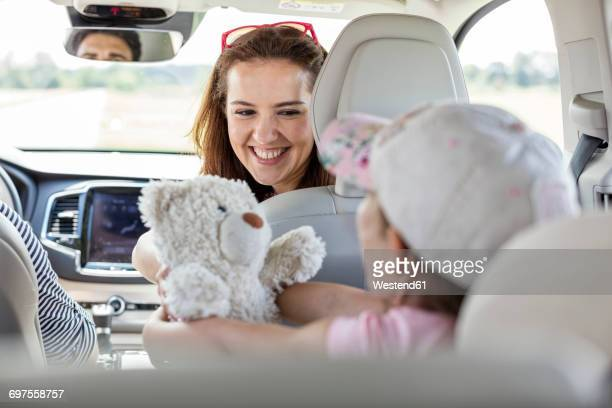 Mother and daughter on road trip sitting in car holding teddy bear