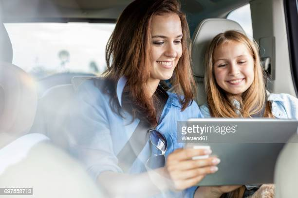 Mother and daughter on road trip sitting in car looking at digital tablet
