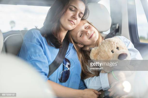 Mother and daughter on road trip sitting in car, sleeping