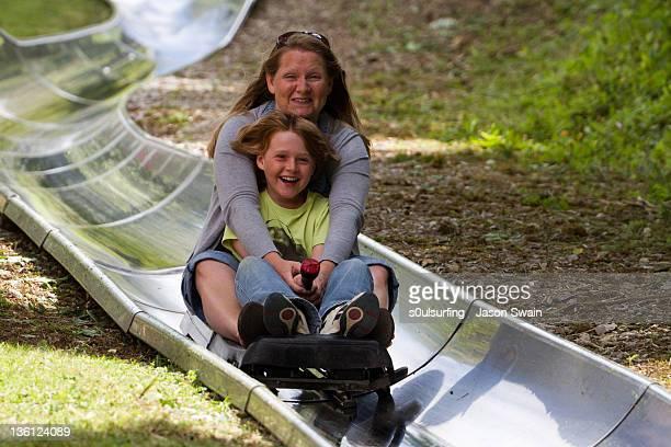 mother and daughter on slide - s0ulsurfing stockfoto's en -beelden