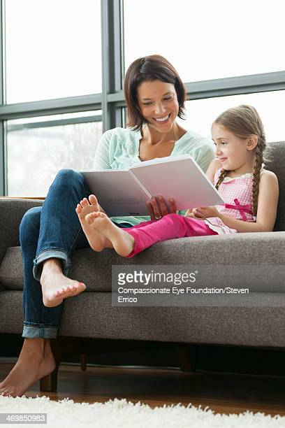 Mother and daughter on sofa reading book