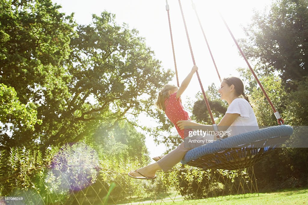 Mother and daughter on swing in sunny park : Stockfoto