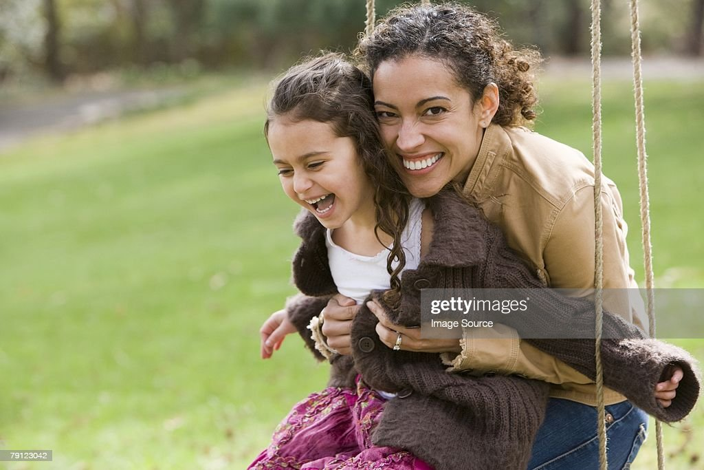 Mother and daughter on swing : Stock Photo