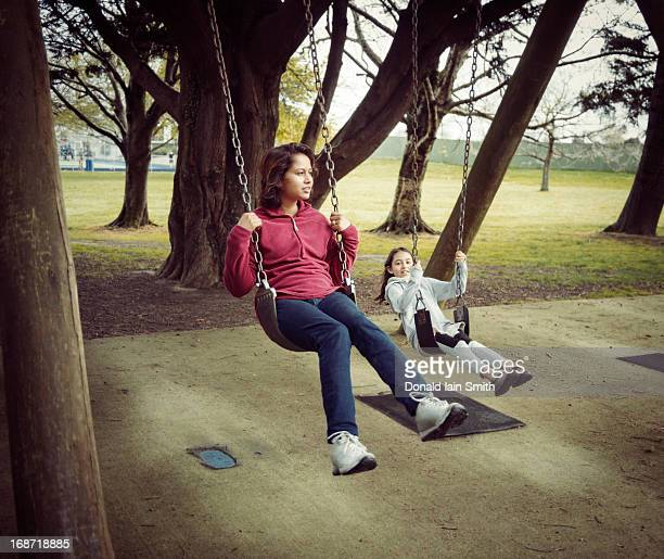 Mother and daughter on swings in park.