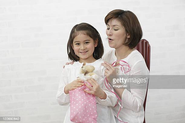 Mother and daughter opening gift