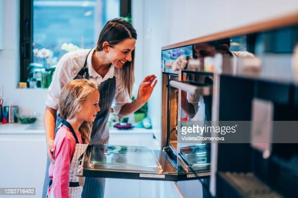 mother and daughter opening oven to check food. - hot wives photos stock pictures, royalty-free photos & images