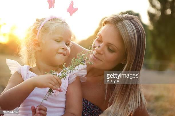 Mutter und Tochter im Freien in einer Wiese.