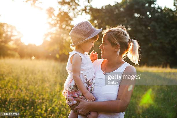 Mother and daughter outdoors in a meadow.