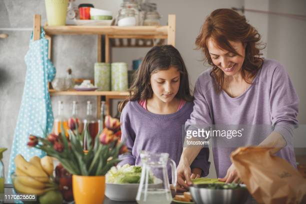 mother and daughter packing a lunch box in the kitchen - pranzo foto e immagini stock