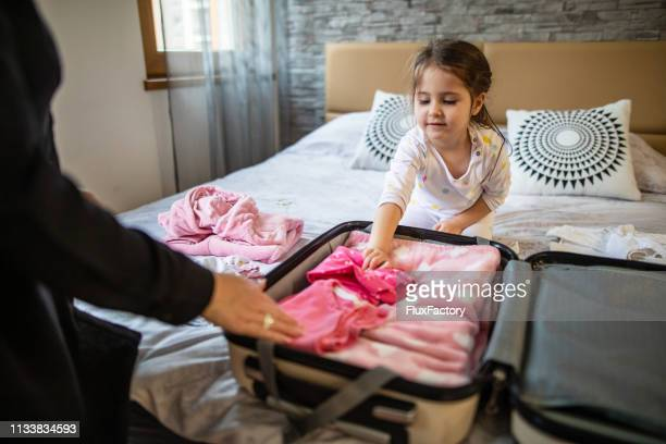 mother and daughter packing a suitcase for a journey - packing stock pictures, royalty-free photos & images