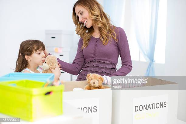 Mother and daughter packing clothesand toys in donation box.
