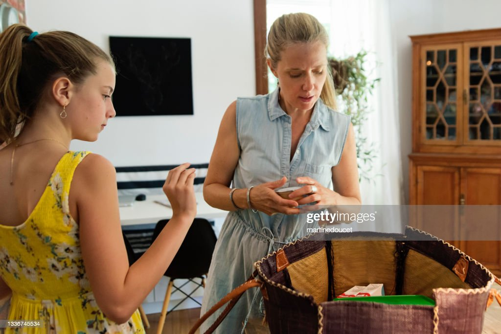 Mother and daughter packing lunch in picnic bag. : Stock Photo