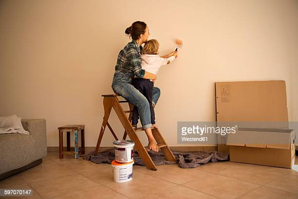 Mother and daughter painting a wall