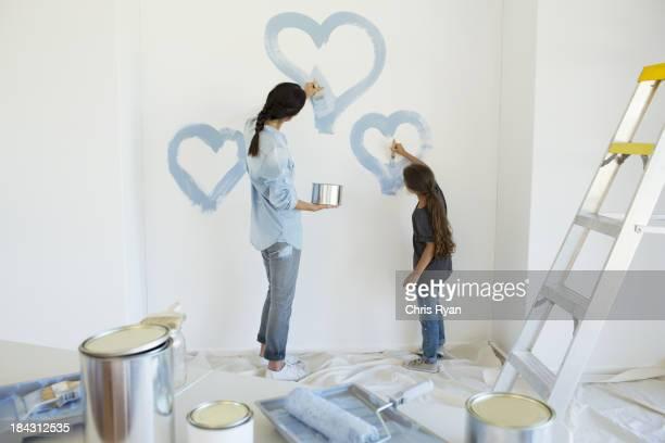 Mutter und Tochter Malerei Herz auf Mauer in Blau