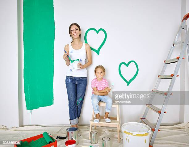 Mother and daughter painting green hearts on wall