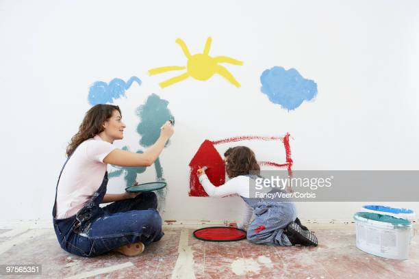 Mother and daughter painting wall together