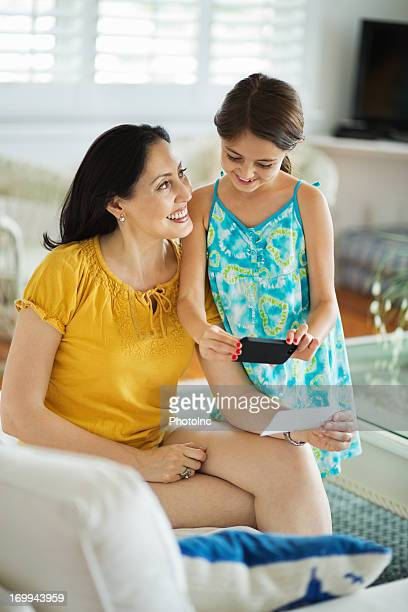 Mother And Daughter Paying Bill Through Mobile Phone
