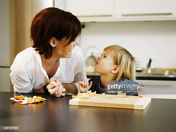 Mother and daughter peeling orange