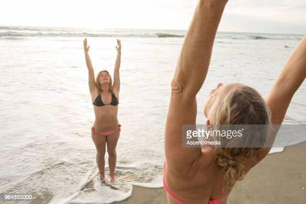 Mother and daughter perform yoga on beach