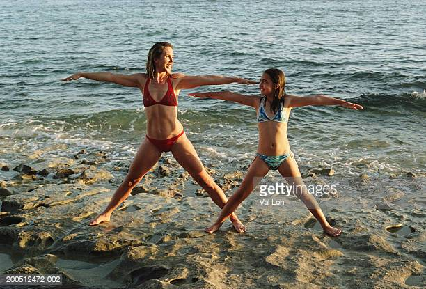 Mother and daughter (9-11) performing yoga on rocks at beach, smiling