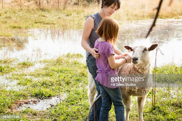 Mother and daughter petting sheep on farm